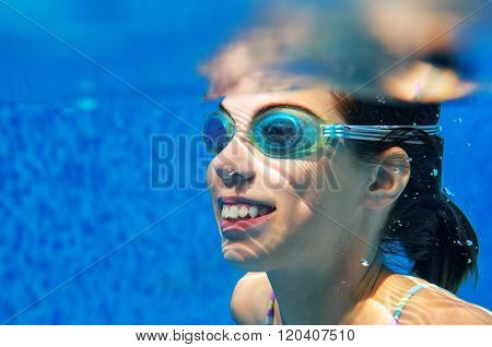 Child swims in pool underwater, happy active girl in goggles has fun under water, kid sport