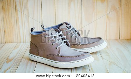gray suede shoes on old wooden background