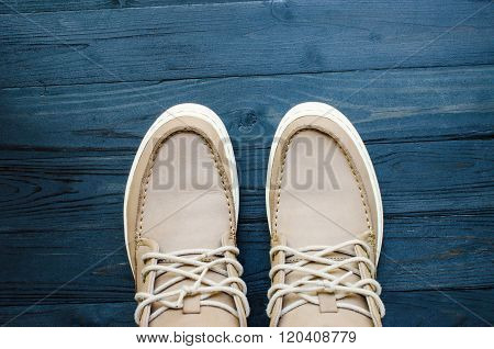 gray Suede Shoes on black wooden background