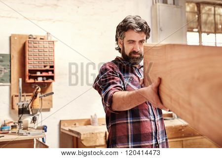 Skilled craftsman inspecting a wooden plank for quality of cut