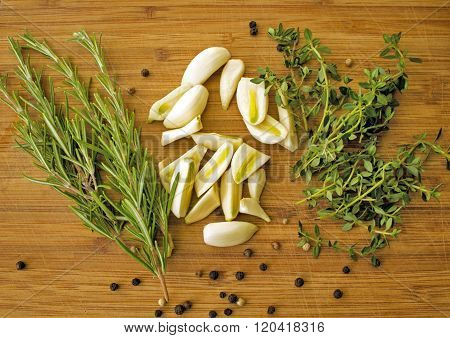 Thyme, rosemary, garlic , pepper on the wooden cutting board. Ready to cook