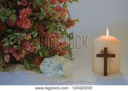 Wedding set up with flowers, candle, wedding garter and cross