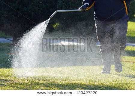 Professional Lawn Care technician spraying fertilizer and weed killer on a Florida Lawn.