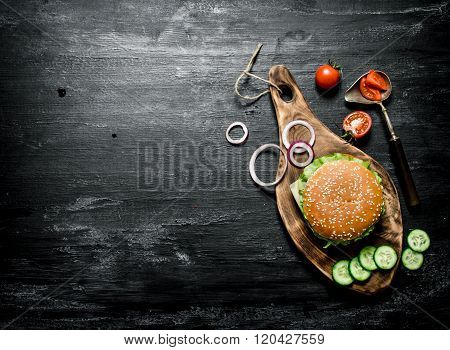 Burger On A Cutting Board With Cucumber And Herbs.
