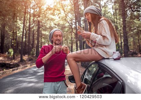 Young couple traveling by car in the forest