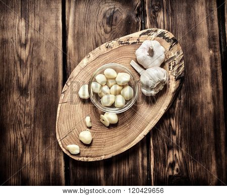 Peeled Cloves Of Garlic On A Wooden Trunk.