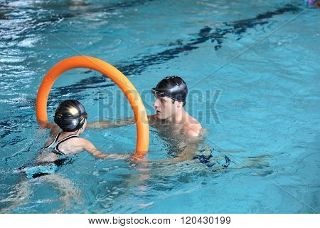 father playing with daughter in swimming pool - healthy lifestyle