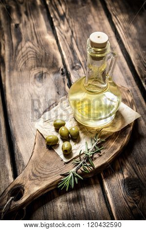 Olive Oil With Rosemary Branch. On Wooden Background.