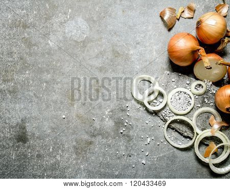 Onion Cut Into Rings On A Stone Stand.