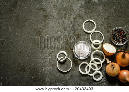 Onion Rings And Spices. On Stone Background.