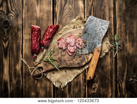 Sliced Salami With A Hatchet And Rosemary.