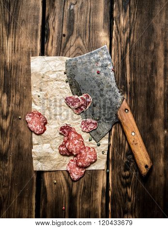 Sliced Salami And An Old Hatchet. On Wooden Background.