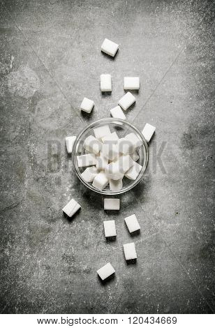 Refined Sugar In A Glass Saucer. On Stone Background.