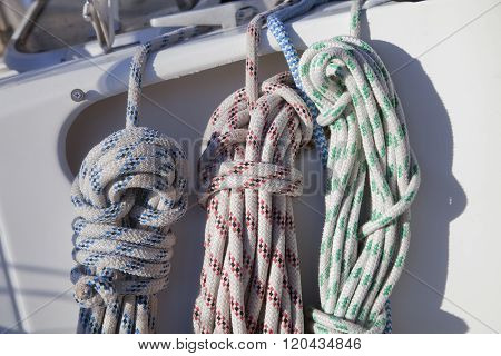 Colorful ropes hanging on yacht railings