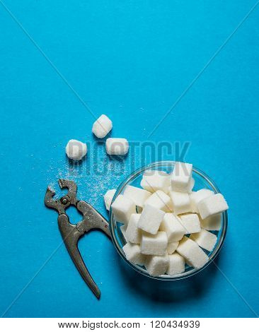 Refined Sugar With Wire Cutters . On Blue Table.