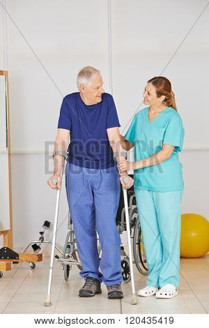 Old man on crutches in physiotherapy with a physiotherapist