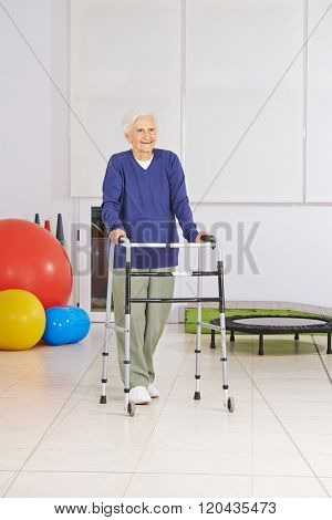 Happy senior woman with walker exercising walking in physiotherapy