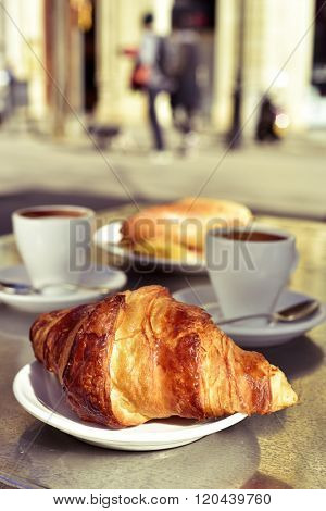 closeup of a table in the terrace of a cafe set for breakfast, with some cups of coffee, a croissant and a spanish omelette sandwich
