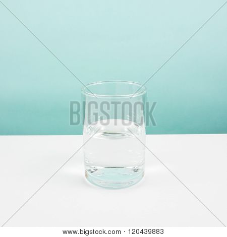 Half empty or half full glass of water on white table