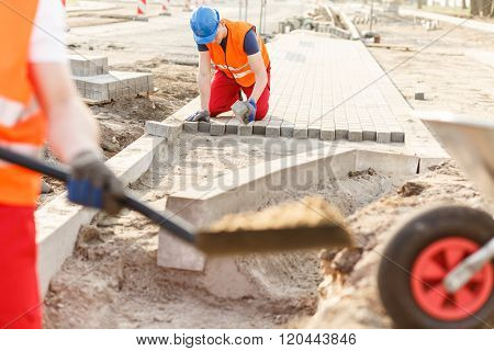 Construction Worker Laying Cobblestones