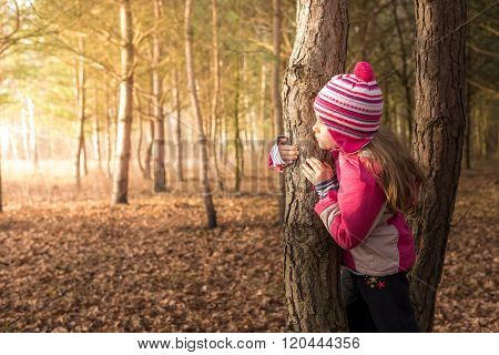 Little cute girl hiding behind a tree in a foreset on a cold autumn morning ** Note: Soft Focus at 100%, best at smaller sizes