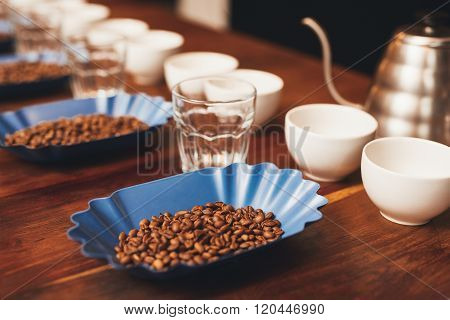 Coffee beans and cups in a row preparation for tasting