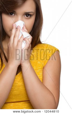 Hispanic teen girl blowing nose