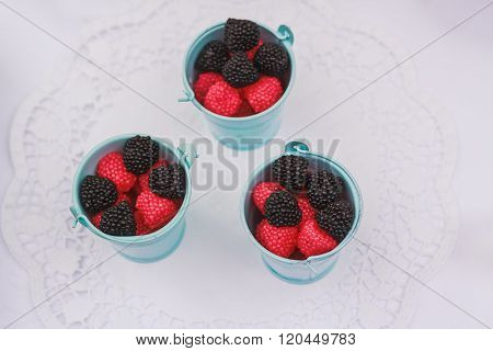 black and red berry shaped candies in small pails