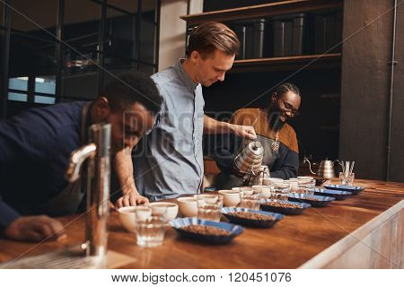Modern roastery with baristas training to pour perfect coffee