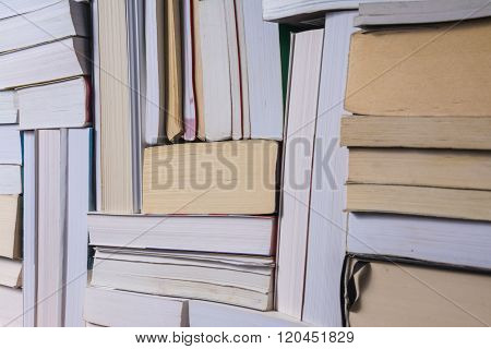 Stack of used old books on bookshelf