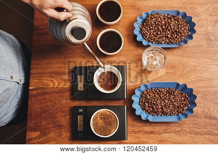 Barista pouring water into cup of ground coffee on scale