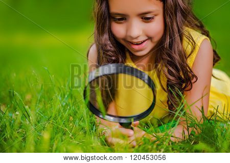 Pretty Little Girl With Magnifying Glass Looks At Grass