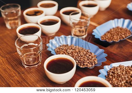 Variety of coffee in cups and beans on table