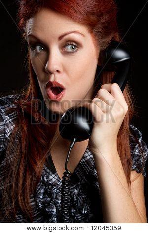 Shocked woman using vintage telephone