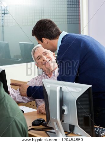 Senior Man Discussing With Instructor In Computer Class