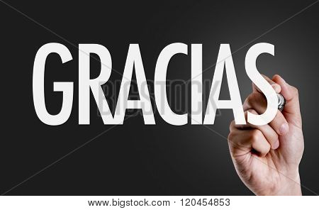 Hand writing the text: Thank You (in Spanish)