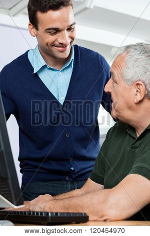 Smiling Tutor Looking At Senior Student In Computer Class
