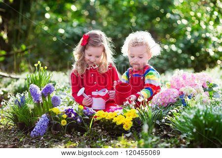 Kids Planting Flowers In Blooming Garden