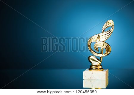treble clef symbol trophy on blue background with copy-space
