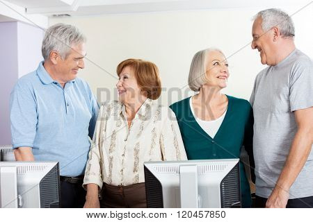 Senior People Looking At Each Other In Computer Class