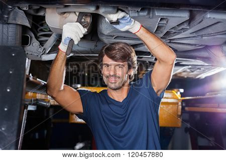 Mechanic Working Under Lifted Car At Garage