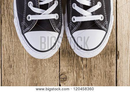 Black Sneakers On Wood Background