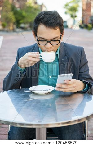 Serious young asian man in business casual attire sitting in outdoor cafe drinking cup of coffee while using mobile phone