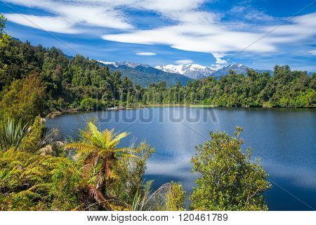Sunny summer day on the Lake Mapourika on the West Coast of New Zealand's South Island, a popular travel destination for fishing kayaking bird wathing and camping