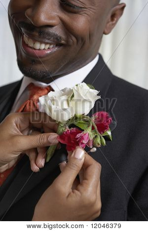 Woman pinning flowers onto man's lapel