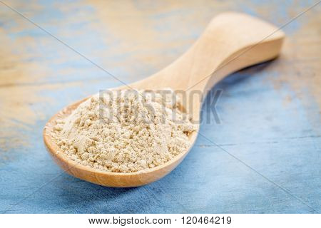 maca root  powder on wooden spoon against blue painted grunge wood