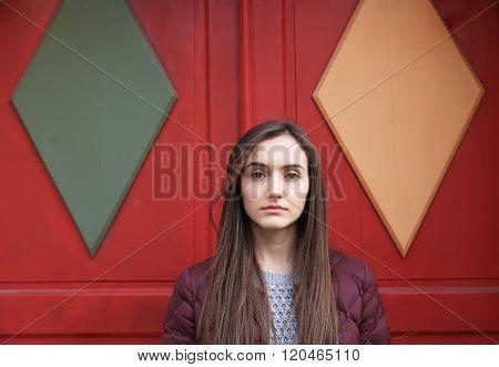 Portrait Of Beautiful Girl On Background Of Red Door