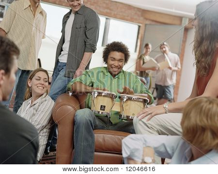 Teenage boy playing drums at party