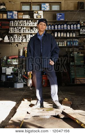 Young female mechanic posing for the camera in garage