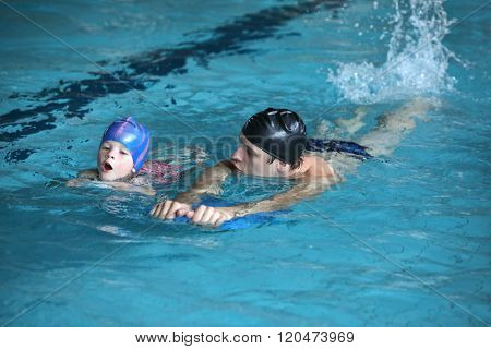 Close up of swimming lesson - child  practicing flutter kick with kick board  with instructor in  indoor swimming pool - front view